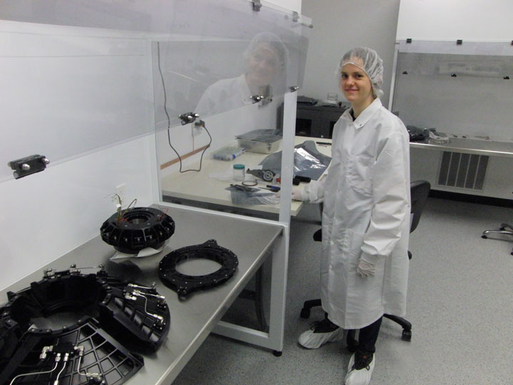 Woman in lab coat assembling spacecraft